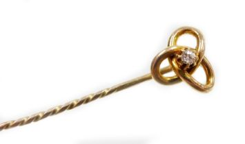 A knot design stick pin, set with single tiny diamond in claw setting with three tier knot on pleate