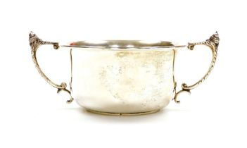 A George V silver trophy cup, the plain circular bowl with angular leafy handles surmounted by acorn
