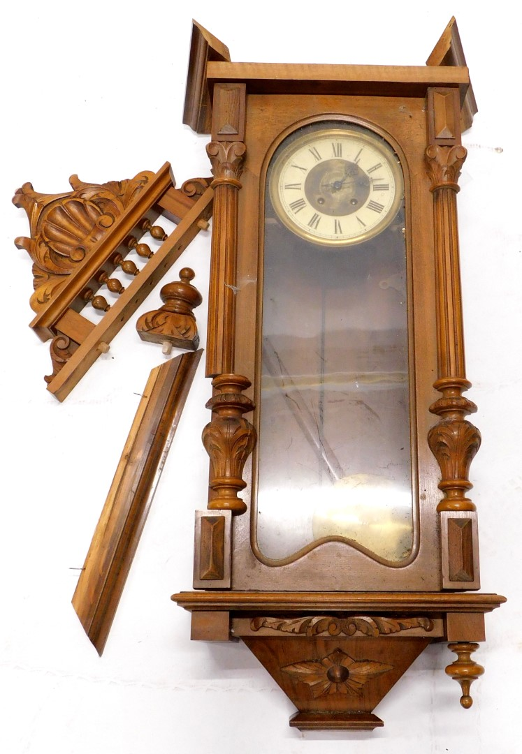 A late 19thC Vienna wall clock, in a walnut case, with carved shaped crest, the door with a glazed