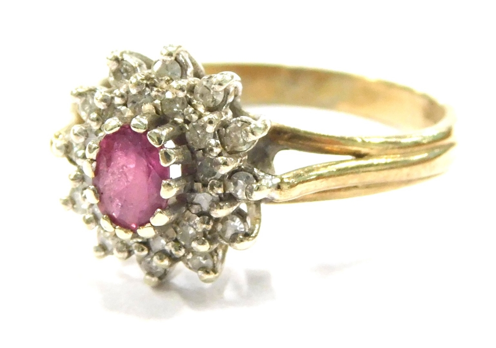 A 9ct gold ruby and diamond cluster ring, set with oval cut ruby in claw setting, surrounded by tiny