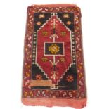 A Persian mat or small rug, with a central pole medallions, 53cm x 98cm.