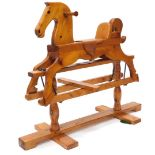 A carved pine child's rocking horse, with leather saddle and ebonised metal mounts, on a trestle
