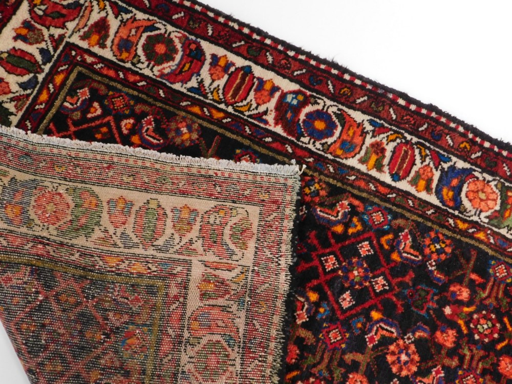 A Persian narrow rug, with an all over design, on a deep navy ground, one wide, two narrow - Image 3 of 3