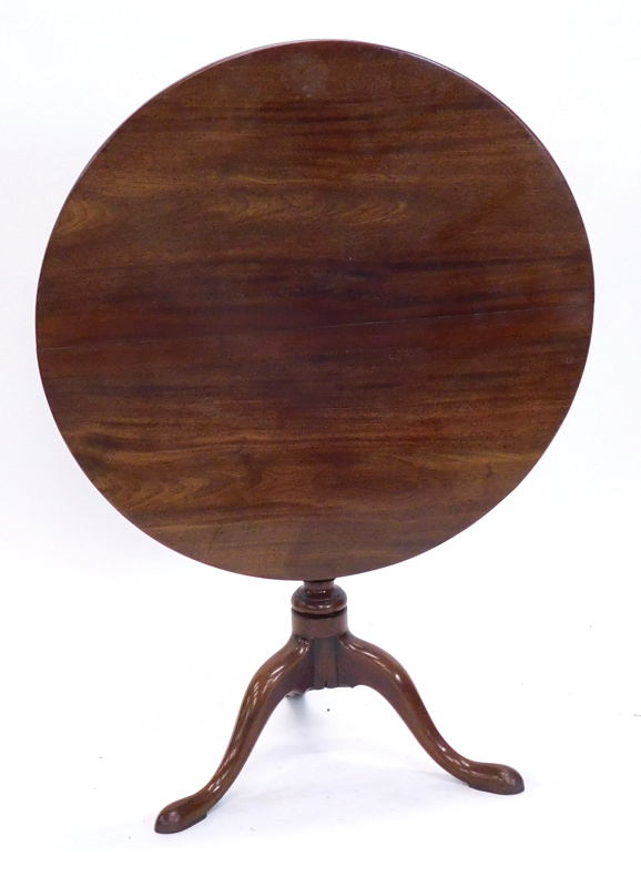A mahogany tilt top occasional table, with a circular top on a turned column and tripod base,