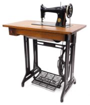 A Singer treadle sewing machine table, the fold-and-reveal machine numbered ED042387, on an oak