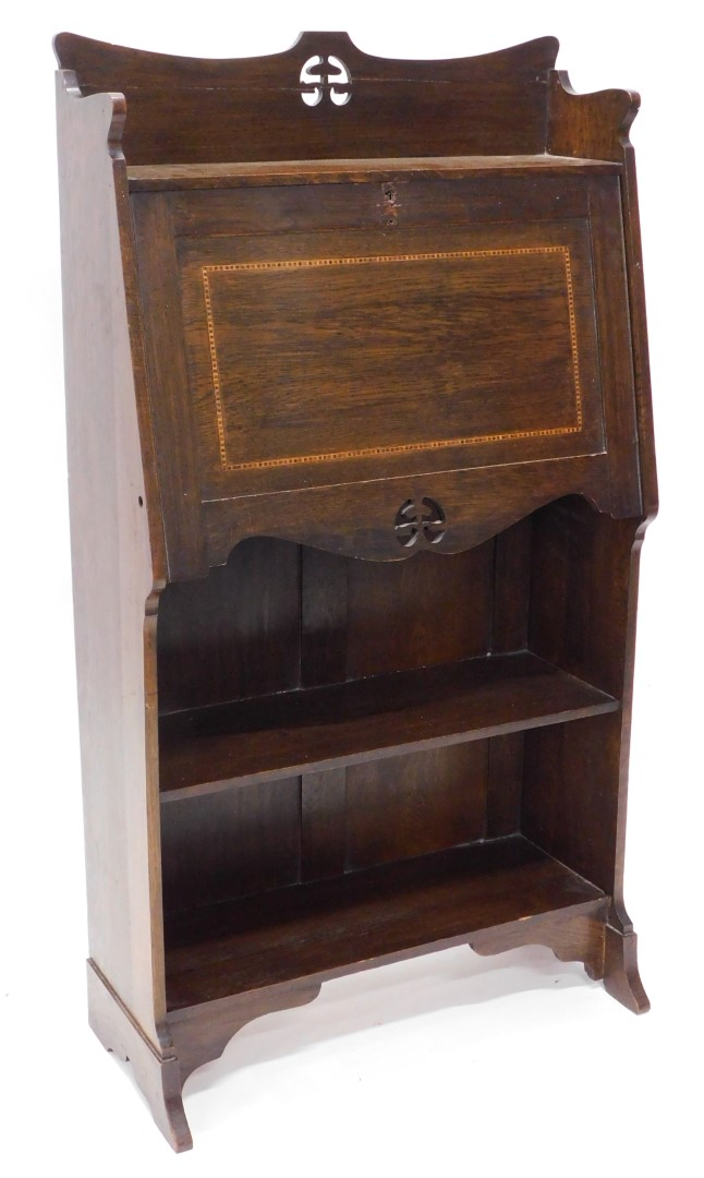 An Edwardian oak and chequer banded students desk, with a pierced crest, a fall enclosing a fitted