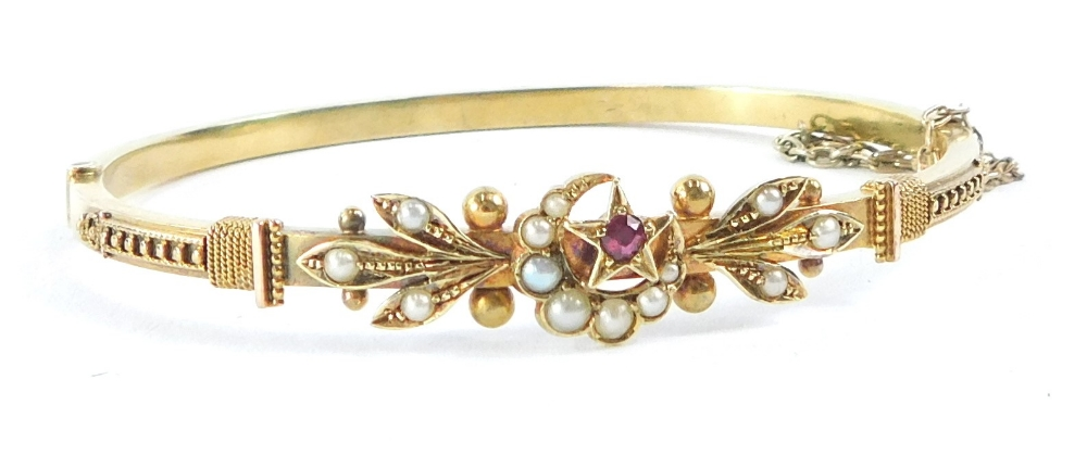 A Victorian/Edwardian hinged bangle, with crescent moon and star decoration, set with ruby and