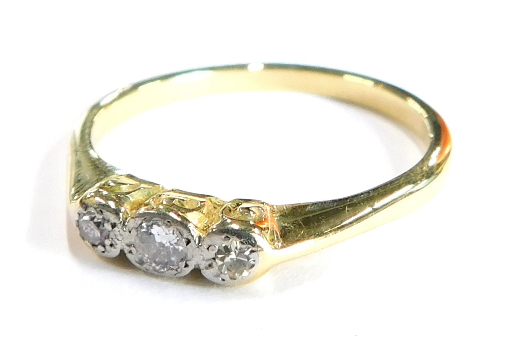 A three stone set dress ring, set with three tiny diamonds, in illusion platinum setting, with