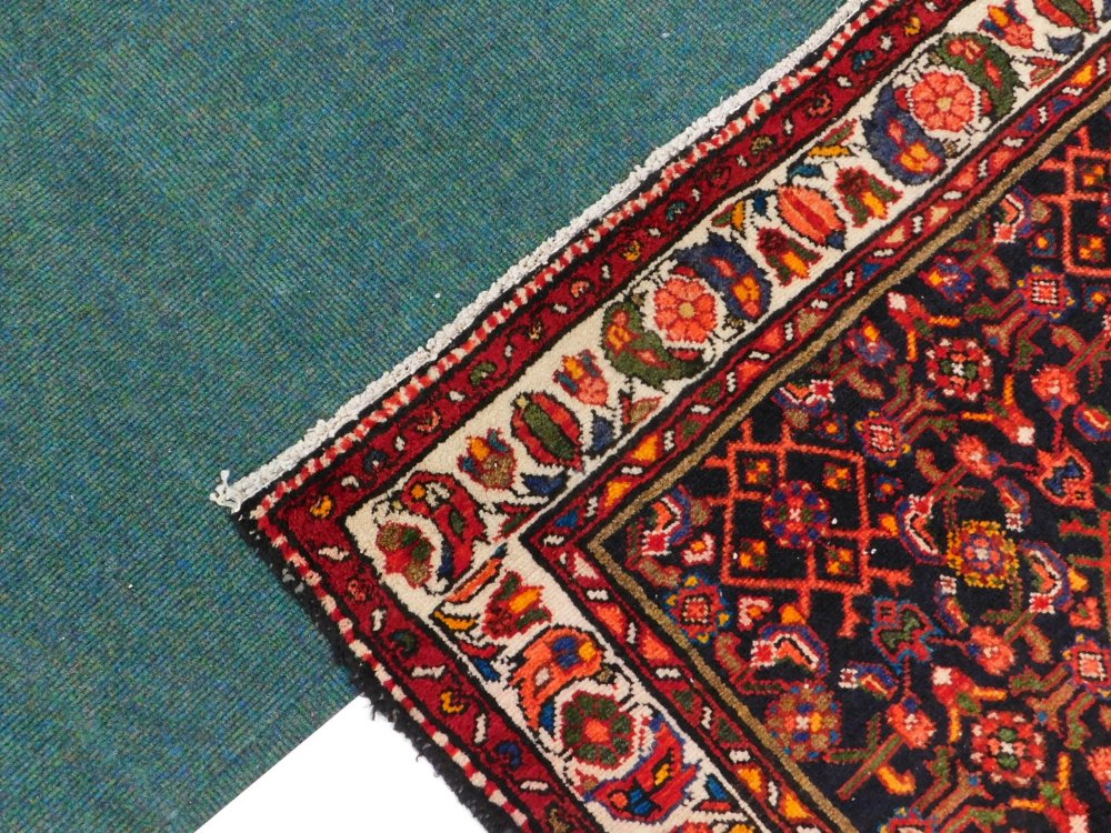A Persian narrow rug, with an all over design, on a deep navy ground, one wide, two narrow - Image 2 of 3
