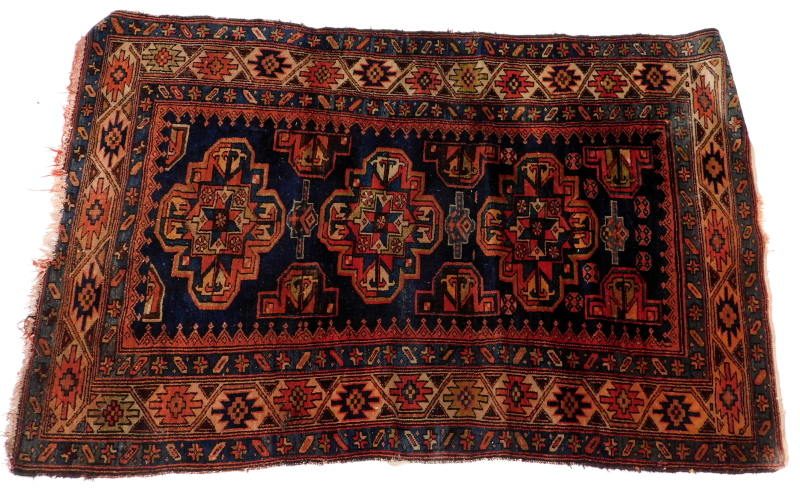A Persian rug, with a design of three medallions, on a blue ground 116cm x 166cm.