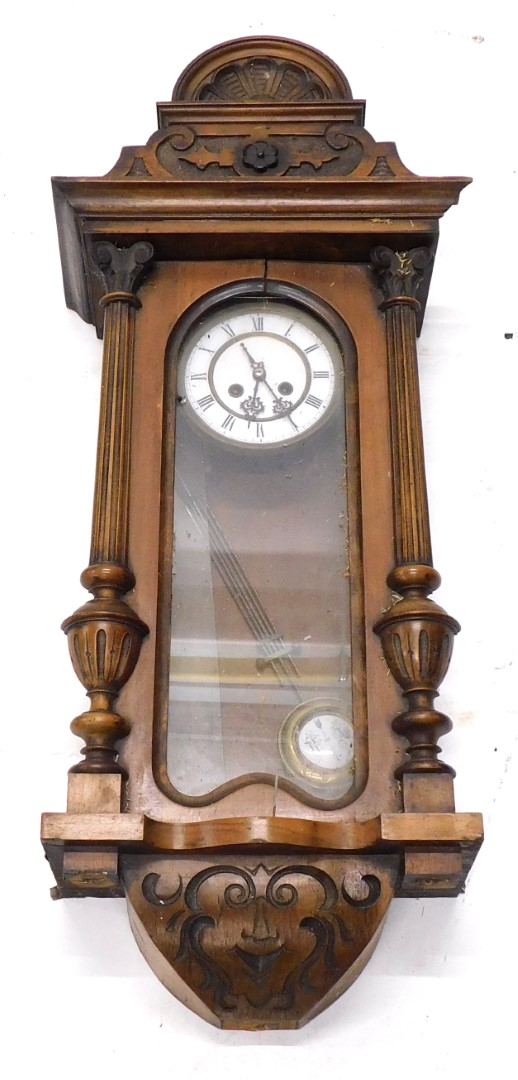 A late 19th/early 20thC Vienna wall clock, in a walnut case with white enamel dial, flanked by two