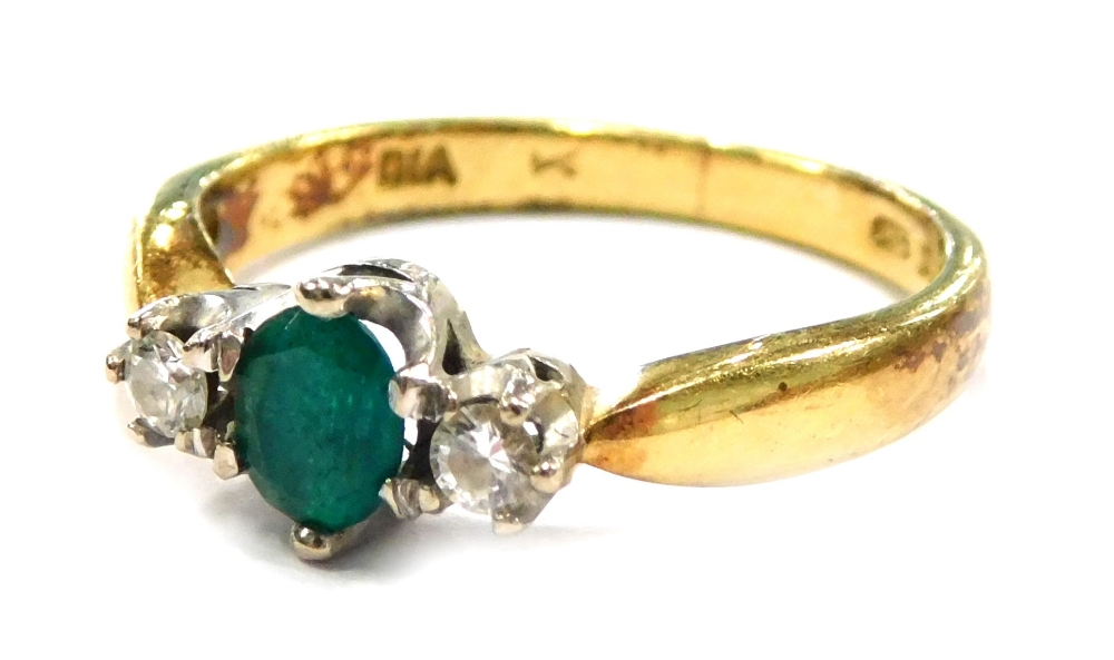 An 18ct gold emerald and diamond set dress ring, the central oval cut emerald in six claw setting,