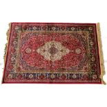 A red ground Kashmere type rug, with a design of a cream medallion, on a red ground with blue