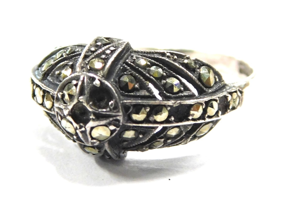 An Art Deco marcasite dress ring, with central circle with four point and three layered design, in