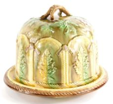 A Victorian majolica cheese dome and cover, decorated with leaves within arched compartments, the