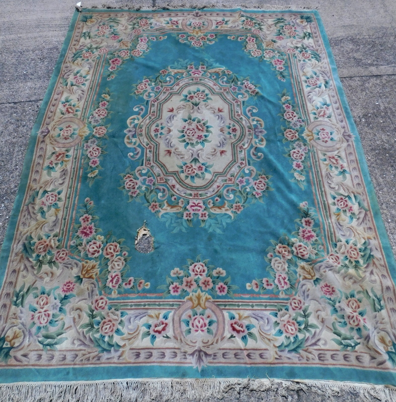 A Chinese carpet, decorated in Aubusson style, with flowers etc., on a green ground, (AF), 375cm x