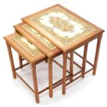A nest of three teak tables, each with a tiled top and chamfered legs, the largest 55cm wide.