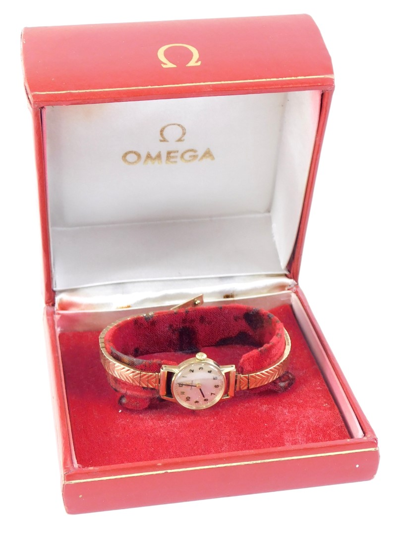 An Omega ladies wristwatch, in a 9ct gold watch head case with silvered dial, on a 9ct gold