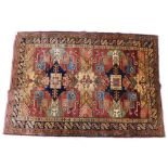 An Afghan Kazak style rug, with a multi coloured design of lozenges, geometric devices, etc., in