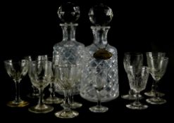 A pair of cut glass decanters and stoppers, and one silver decanter label for brandy, with beaded