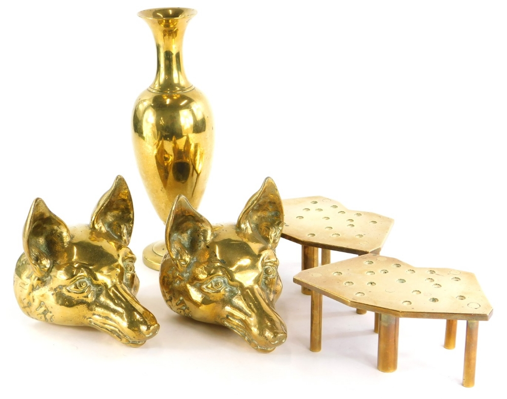 A pair of cast brass fox head door stops, a pair of pierced trivets and a vase. (5)
