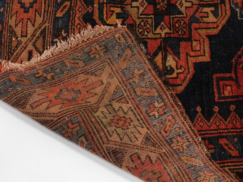 A Persian rug, with a design of three medallions, on a blue ground 116cm x 166cm. - Image 3 of 3