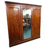 A Victorian figured mahogany triple wardrobe, with a moulded cornice above a central mirror, flanked