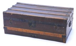 A canvas and wooden bound trunk, with metal brackets and side handles, 79cm wide.