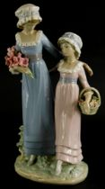 A Lladro porcelain figure group, of a lady with a young girl holding flowers, on oval base, 32cm