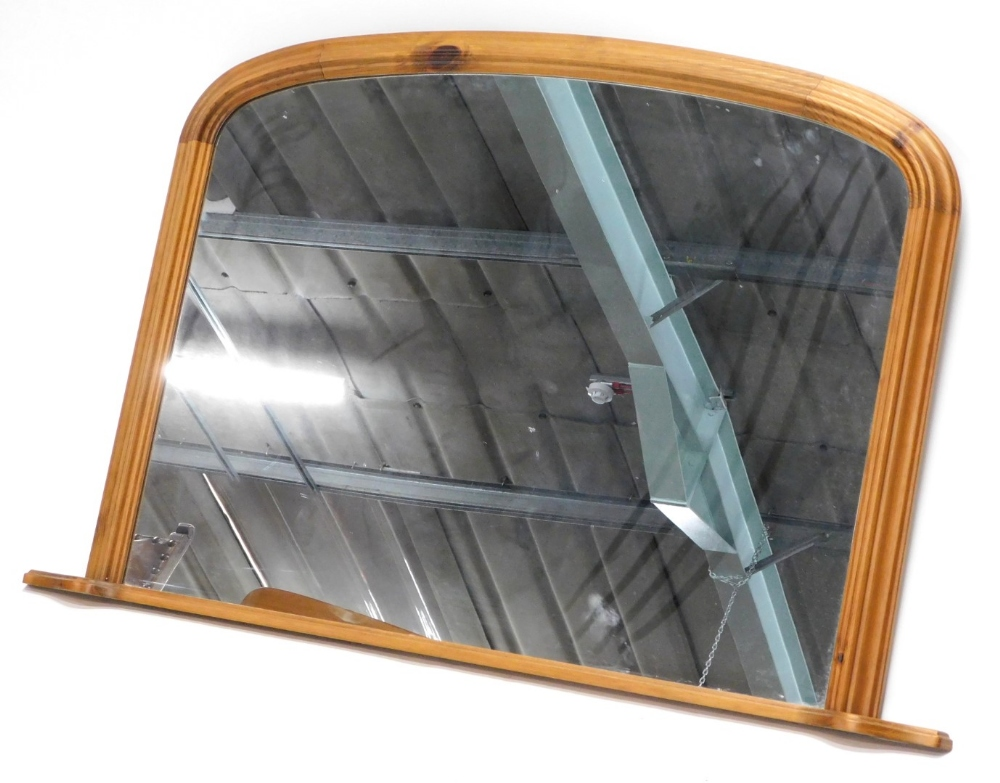 A pine overmantel mirror, the arched frame with a moulded edge, 82cm high, 125cm wide.
