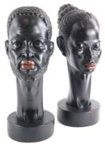 A pair of 1950s/60s ebonised plaster busts, modelled in the form of an African man and lady, each