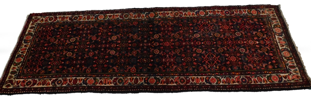 A Persian narrow rug, with an all over design, on a deep navy ground, one wide, two narrow