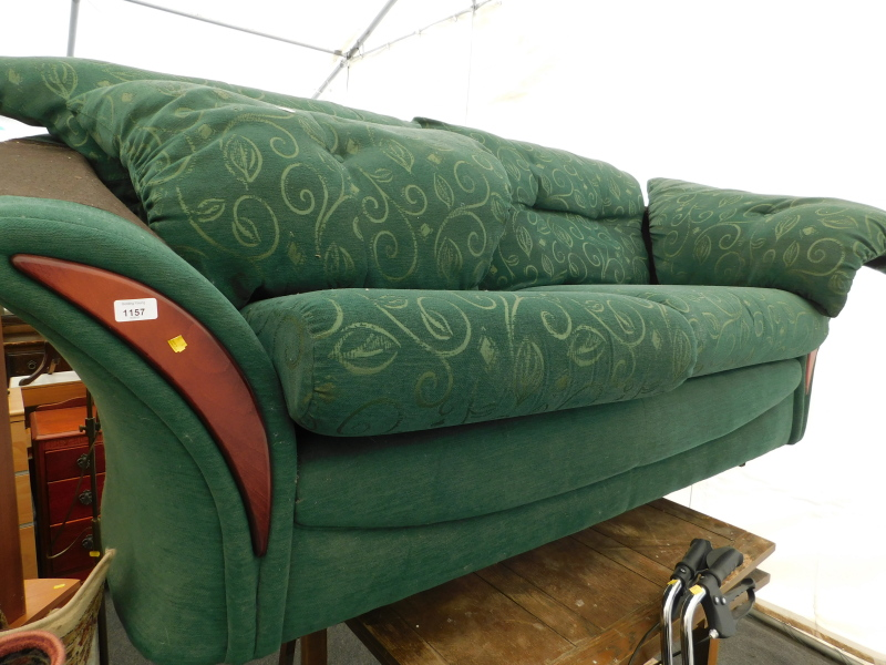 A two seater sofa, in green leaf pattern fabric.