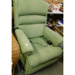 An electric reclining armchair, in green diamond pattern fabric.