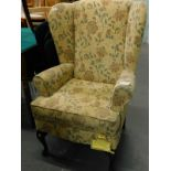 A Sherborne wing back armchair, in floral fabric on cabriole legs. The upholstery in this lot does