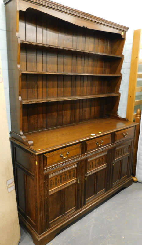 An oak Welsh dresser, the top with pot board, the base with three drawers above three hinged
