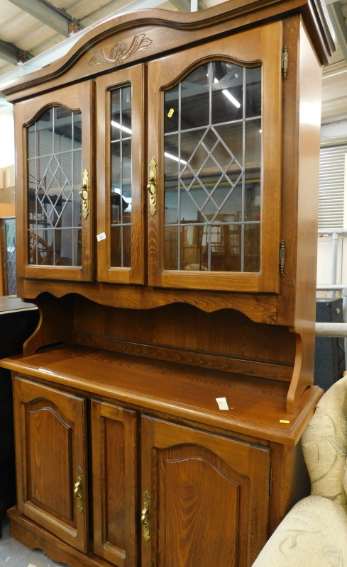 An oak dresser, the top with two leaded glazed doors, the base with two hinged doors.