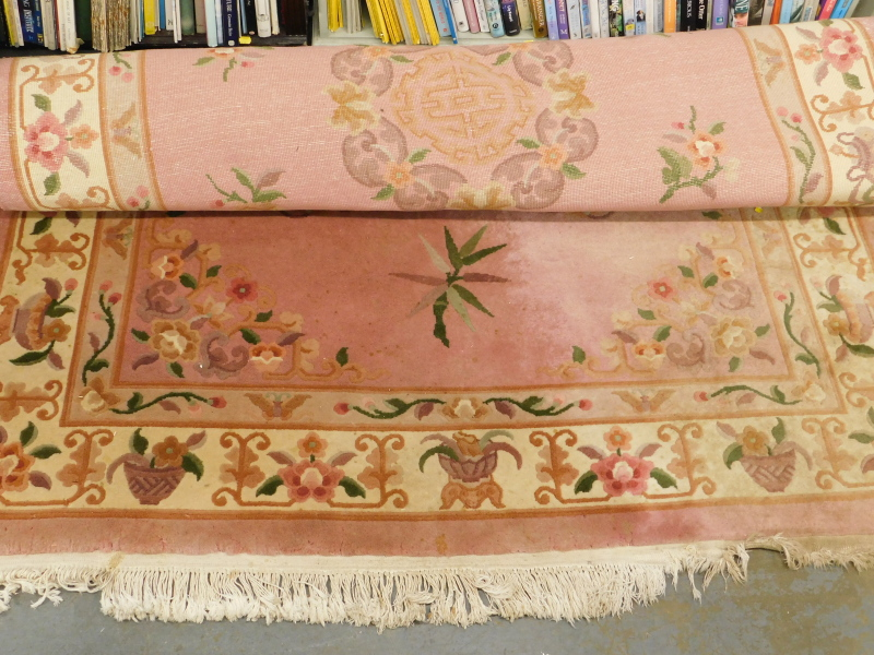 A Chinese wool rug, on a pink ground, decorated with flowers.