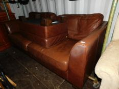 A three seater sofa, upholstered in brown leatherette, together with a matching footstool. (2)