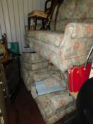A four piece suite, comprising three seater settee, two armchairs and a foot stool, upholstered in a