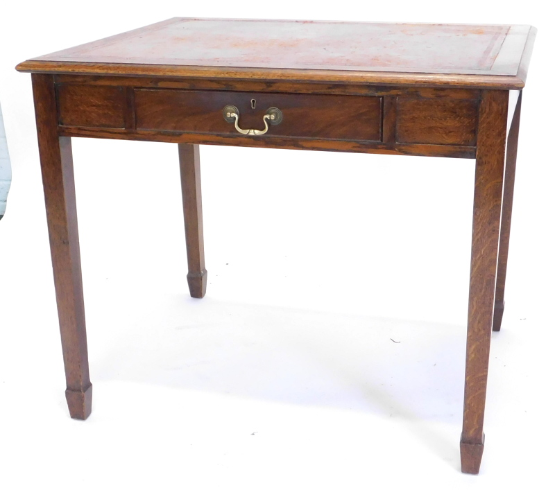 An oak and mahogany writing table, the top with a brown leather inset and moulded edge, above an ass