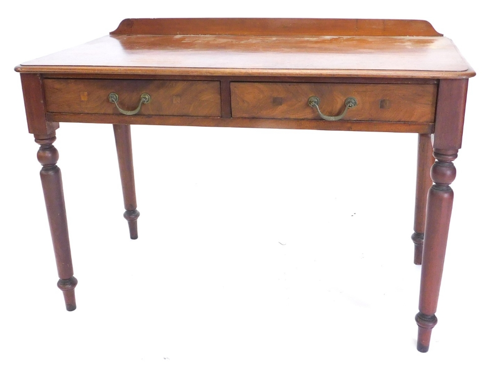 A mahogany table, with a raised back above two frieze drawers, on turned tapering legs, 70cm high, 1