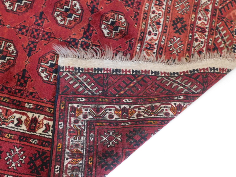 A Bokhara rug, with a typical design of three rows of medallions on a red ground, with multiple bord - Image 3 of 3