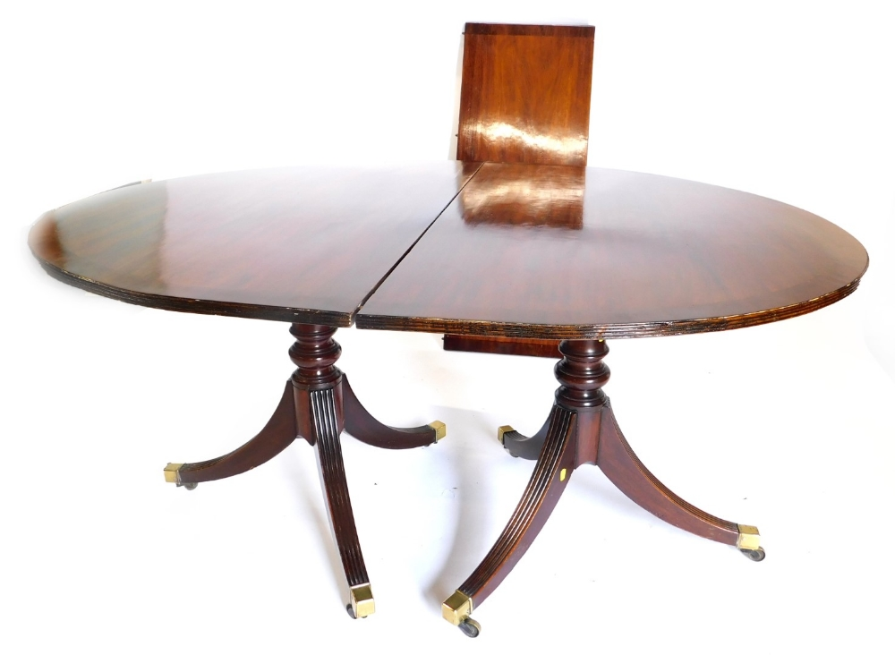 A mahogany extending dining table in Regency style, the top with a reeded edge, on two turned pillar