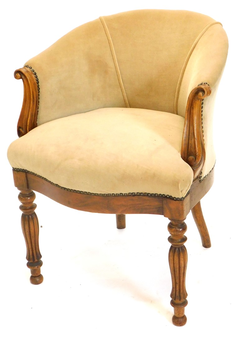 A Victorian walnut tub shaped chair, upholstered in beige fabric, with shaped arm supports, a serpen