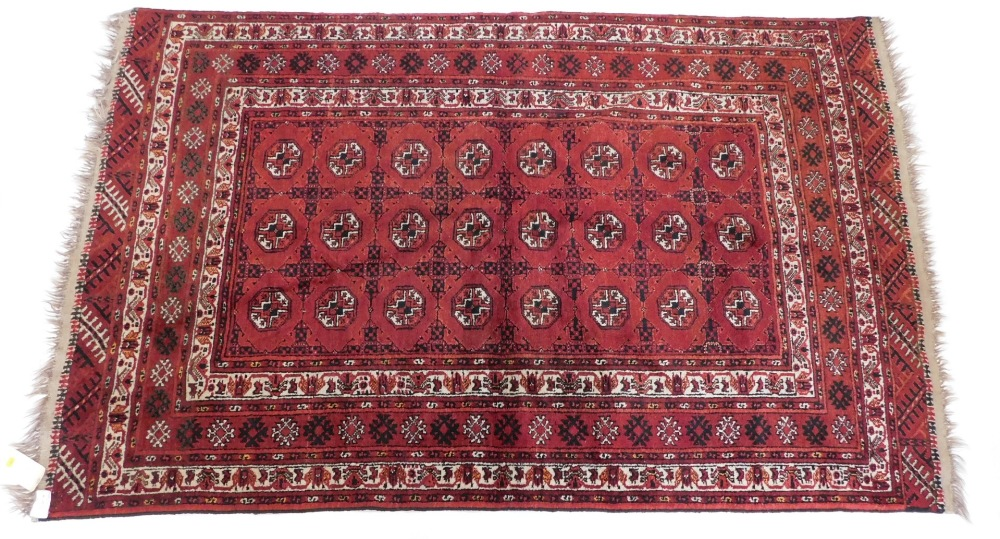 A Bokhara rug, with a typical design of three rows of medallions on a red ground, with multiple bord