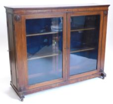 An early 19thC mahogany freestanding library bookcase, the top with a moulded crest above two glazed
