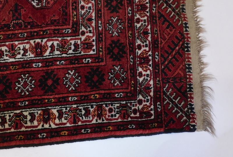 A Bokhara rug, with a typical design of three rows of medallions on a red ground, with multiple bord - Image 2 of 3