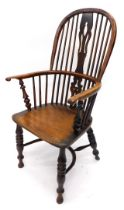 A mid 19thC yew, ash and elm Windsor armchair, with a pierced splat, solid dish seat, on turned legs