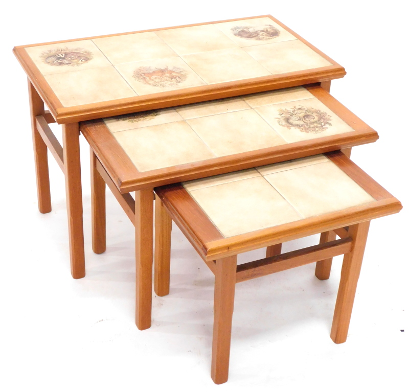 A nest of three teak tables, each with a painted tile design of badgers, white tailed Deer and otter